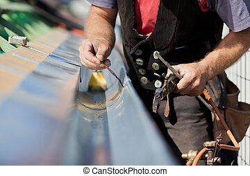 Close-up of a roofer welding the gutter on a new roof