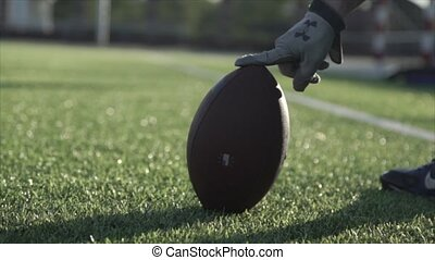 Close-up of a rugby ball on the field holds a man's hand HD