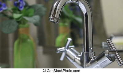 Close up of a running faucet - Water pouring out of bathroom...