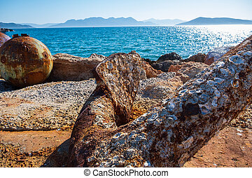 Close-up of a rusty anchor on the shore at Aegina harbour in Greece