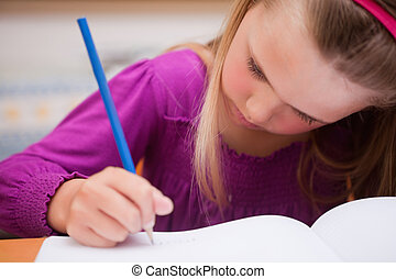 Close up of a schoolgirl writing on a book
