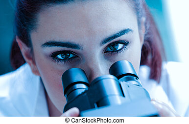 Close up of a scientist posing with a microscope