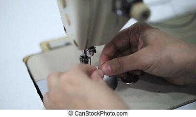 Close up of a seamstress hands putting a thread in a needle of a sewing machine