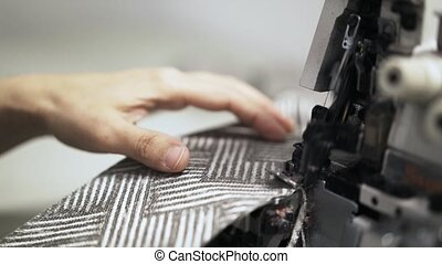 Close up of a seamstress making an even cloth edge on a sewing machine