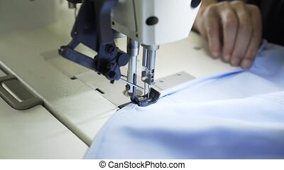 Close up of a seamstress sewing a shirt at a factory