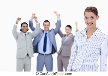 Close-up of a secretary smiling and business people with the thumbs up in the background