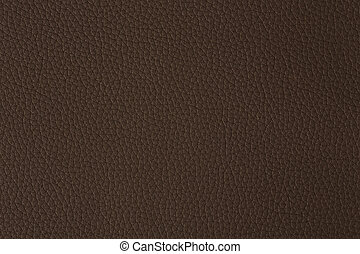 Close up of a section of a brown leather swatch showing grain and a shaft of light across.