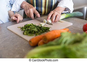 Close up of a senior lady cutting vegetables on a board