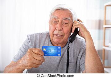 Man With Credit Card Using Landline Phone