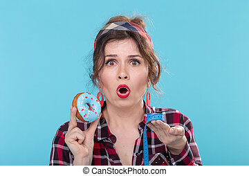 Close-up of a shocked and upset young beautiful woman holding a blue donut in her hands and measuring tape. Concept of rejection of high-calorie foods and healthy lifestyle choice.