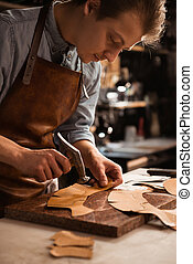 Close up of a shoemaker man working with leather using...
