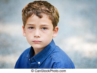 close up of a six year old boy with a serious expression looking at the camera
