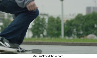 Close up of a skateboarders feet while skating on concrete...
