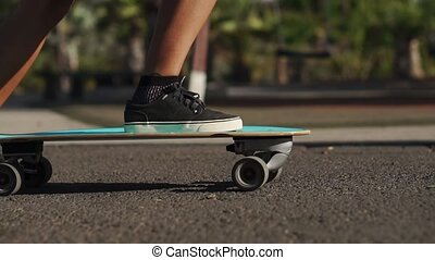 Close-up of a skater's foot on the Board. Longboard rides on the road in slow motion
