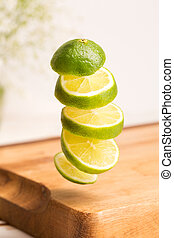 Close up of a sliced whole lime flying