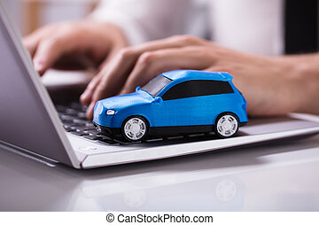 Blue Car On Laptop Keypad