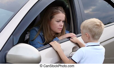 Close-up of a small boy talking to his mother who is sitting in the car.