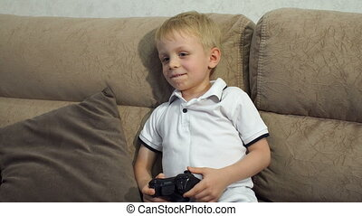 Close-up of a small child playing computer video games at home on the couch.