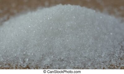 Close up of a small pile of sugar forming into a pyramid.