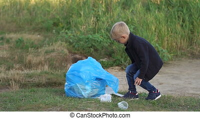 Close-up of a small responsible boy helping to clean up the garbage in the Park.