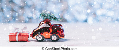 Close-up of a small toy car carries a xmas tree on the roof