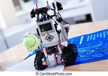 Close up of a smart innovative robot holding a tennis ball -...