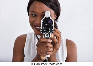 Woman Looking Through Lens Of Retro Camera