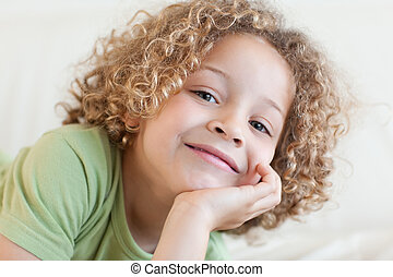 Close up of a smiling boy lying on a sofa