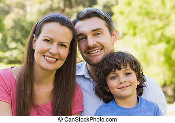 Close-up of a smiling couple with son in park
