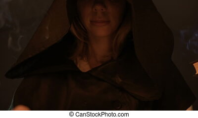 Close-up of a smiling face of a girl in a black magic hood in the light of candles in a dark room. Halloween Holidays and Masquerade. Mystic. Small DOF