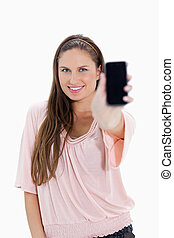 Close-up of a smiling girl showing a smartphone
