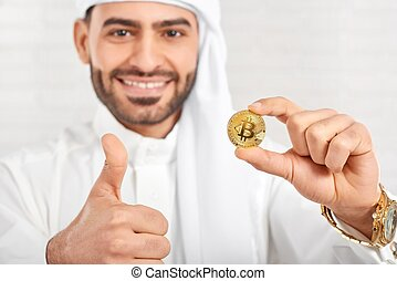 Close-up of a smiling Muslim man keeps bitcoin on the white background.