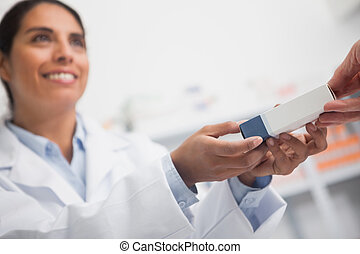 Close up of a smiling pharmacist giving a box to someone in...
