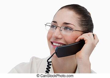 Close up of a smiling secretary making a phone call