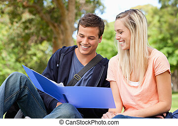 Close-up of a smiling tutor helping a teenager to revise in...