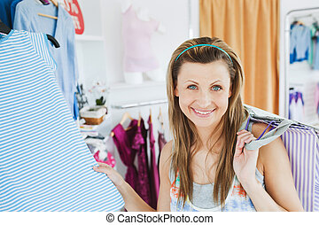 Close-up of a smiling woman doing shopping looking at the camera in a clothes store