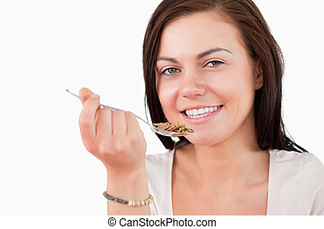 Close up of a smiling woman eating cereal