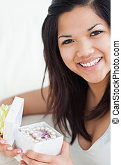 Close-up of a smiling woman holding an open gift box