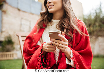 Close up of a smiling woman holding mobile phone