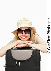 Close up of a smiling woman leaning on a suitcase