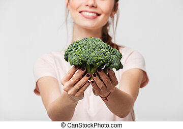 Close up of a smiling woman showing broccoli