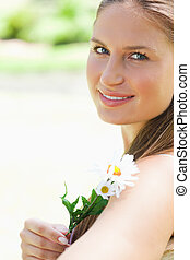 Close up of a smiling woman with a flower