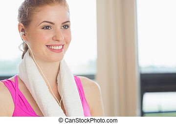 Close-up of a smiling woman with towel around neck listening to music in fitness studio