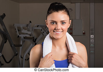 Close-up of a smiling woman with towel in gym