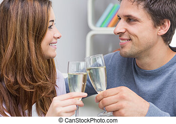 Close-up of a smiling young couple toasting flutes
