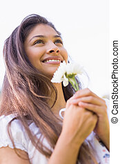 Close-up of a smiling young woman holding flowers
