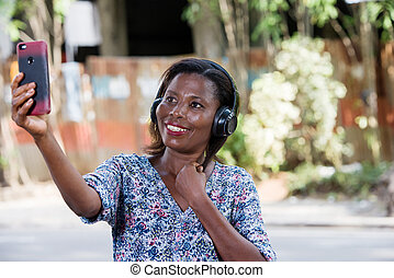 close-up of a smiling young woman with mobile phone.