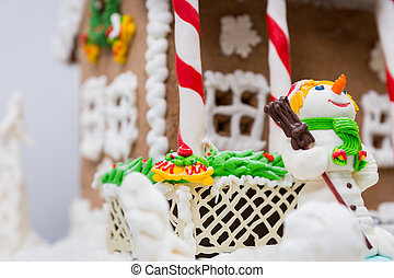 Close up of a snowman from sugar mastic near big gingerbread house