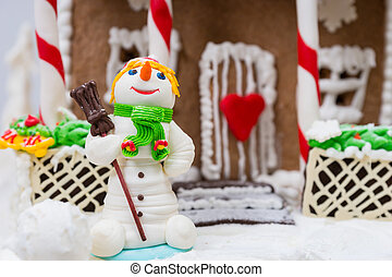 Close up of a snowman from sugar mastic near gingerbread house