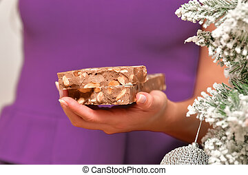 Close up of a split bar of traditional nougat being held by an o